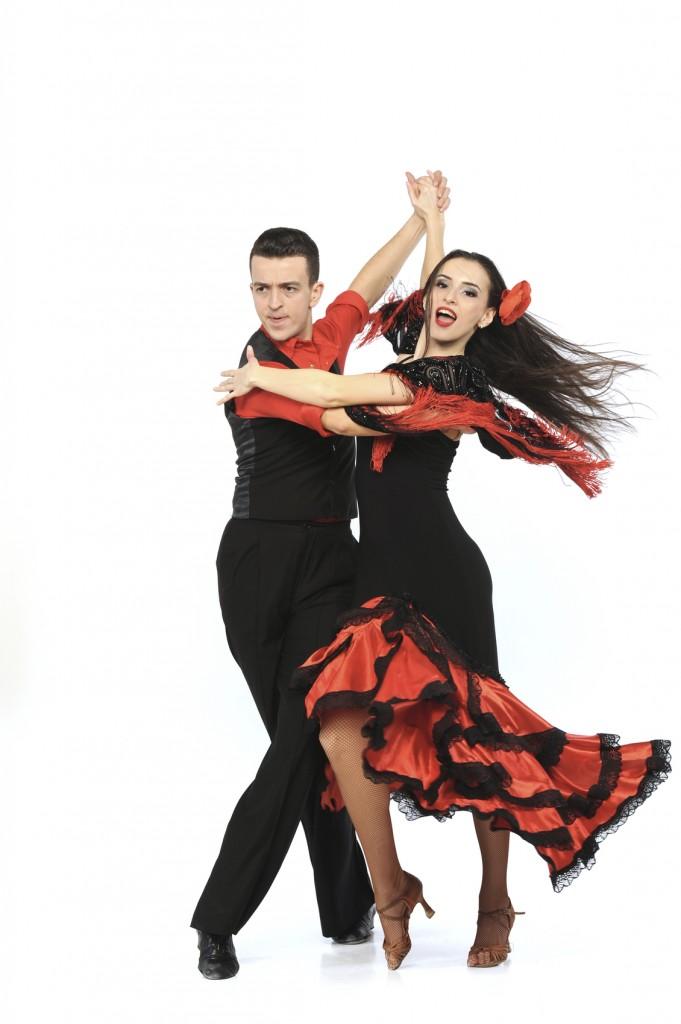 Costumed couple performing flamboyant ballroom dance
