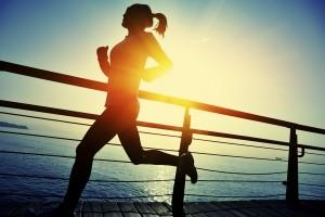 healthy lifestyle asian woman running at wooden boardwalk seaside