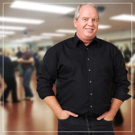 Man in black dress shirt posed in front of dance studio